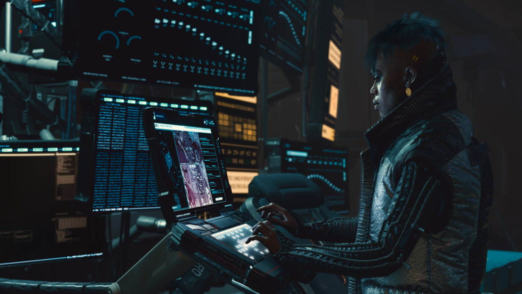 A hacker in front of advanced computers in Cyberpunk 2077.